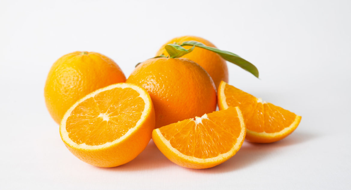 Cut and whole orange fruits with green leaves isolated on white background. Closeup shot. Natural vitamin or organic food concept